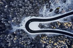 Curved road in winter mountain landscape. Aerial view of forest and trees with a winding street surrounded by snow. Curved road in winter mountain landscape royalty free stock image