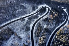Curved road in winter mountain landscape. Aerial view of forest and trees with a winding street surrounded by snow. Curved road in winter mountain landscape stock images