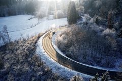 Curved road in winter mountain landscape. Aerial view of forest and trees with a winding street surrounded by snow. Curved road in winter mountain landscape royalty free stock photo