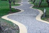 Curved Rock Road resort walk way green tree Stock Images