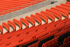 Curved rows of orange Stadium seats. In empty section of stadium stock image