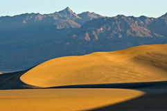 Curved Sand Dunes Under Mountain
