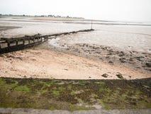 Curved seaside scene pipe groyne beach seaweed pebbles Royalty Free Stock Photos