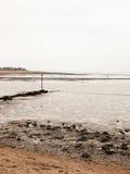 Curved seaside scene pipe groyne beach seaweed pebbles Royalty Free Stock Images