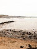 Curved seaside scene pipe groyne beach seaweed pebbles Stock Photos