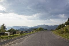 Curved serpentine mountain forest road in Ukrainian Carpathian. Asphalt highways and mountains under the blue sky. Empty Stock Photography
