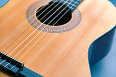 Curved shape part of guitar yellow glossy wooden deck on blue. Curved shape part of acoustic guitar yellow glossy wooden deck on blue background, fragment royalty free stock photos