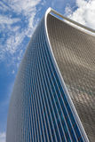Curved skyscraper against blue sky. Low view on a skyscraper against the blue sky with curved lines Stock Photography