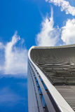 Curved skyscraper against blue sky. Low view on a skyscraper against the blue sky with curved lines Royalty Free Stock Image