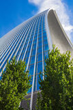 Curved skyscraper against blue sky. Low view on a skyscraper against the blue sky with curved lines Stock Image