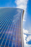 Curved skyscraper against blue sky. Low view on a skyscraper against the blue sky with curved lines Stock Images