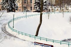 Curved snowy alley in city park. Royalty Free Stock Image