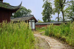 Curved stone path in weed outside aged Chinese building at noon Stock Images
