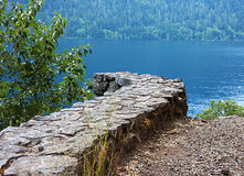 Curved Stone Wall Near Lake. This curved stone wall leading to a blue lake is an interesting nature photo of various colors, shapes and textures Stock Photos