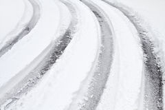 Curved Tire Tracks On A Snow Covered Road. Multiple curved vehicle tire tracks on a snow covered road one wintry day in January. Weather conditions such as this Stock Images