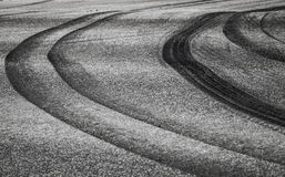 Curved tires tracks on dark asphalt road Royalty Free Stock Photography