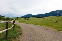 Curved trail leading to mountain landscape. Curved trail with wood fence leading along green grass to a beautiful mountain landscape stock images