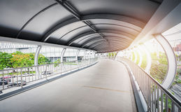 Curved walkway bridge with curved steel roof. Over road and sunlight royalty free stock photos