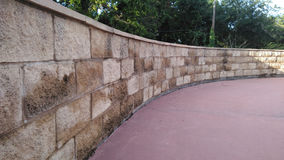 Curved wall. Exterior curved stone wall next to walkway Stock Photo