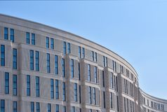 Curved wall of a modern building against the blue sky royalty free stock photo