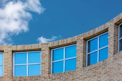 Curved wall with windows. Curved brick wall with double glazed windows Royalty Free Stock Image