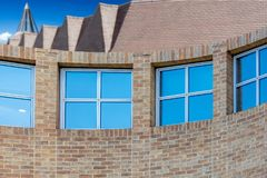 Curved wall with windows. And roofs of other buildings behind Stock Photo