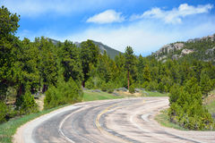 Curved Weathered Asphalt Mountain Road on a Sunny Day Royalty Free Stock Images