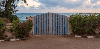 Curved weathered blue wooden garden gate with green bushes at both sides and background of sea and partly cloudy sky at sunrise. Curved weathered blue wooden royalty free stock images