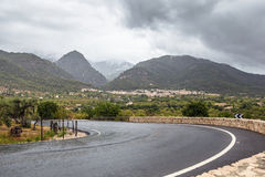 Curved wet asphalt road in a rainy day Royalty Free Stock Photos