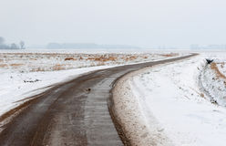 Curved and wet country road in a bald snow landscape Stock Photo