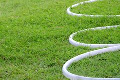 A curved of white rubber tubes on green grass field stock photo