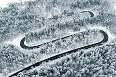Curved winding road in the forest in winter time stock photo