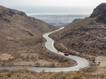 Curved winding road with a red car in the mountains in Gran Canaria. Curved winding road GC-60, with a red car in the mountains in Gran Canaria royalty free stock photo