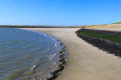 The curveld waterline  along the sandy beach in springtime stock photography
