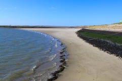 Curveldvattenlinjen längs den sandiga stranden i vår arkivbild