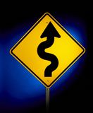 Curves ahead. Yellow road sign shot on blue glowing background warning of curvy road ahead stock photos