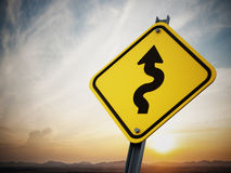 Curves ahead road sign. On setting sun background Royalty Free Stock Photography