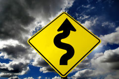Curves Ahead in Storm. Yellow street sign with curves against stormy sky Royalty Free Stock Photos