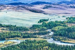 The curves of the ribbon of the river in a mountain valley. Beautiful view of the valley from above stock images