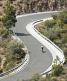 Curves in the road with a cyclist Royalty Free Stock Photography