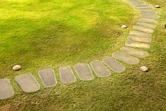 Curvi il passaggio pedonale di pietra sul campo di erba in giardino Fotografie Stock