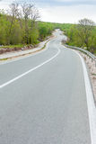 Curving black asphalt road with white marking lines from low poi Royalty Free Stock Photos