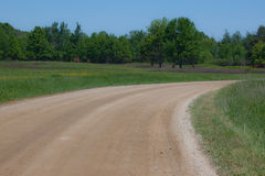 Curving Country Road. A photo of a curving dirt road surrounded by fields and trees Royalty Free Stock Photography