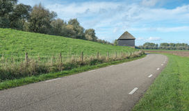Curving country road next to a dike Royalty Free Stock Photo