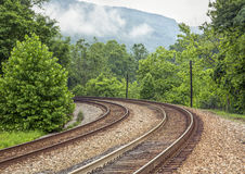 Curving Double Railroad Tracks. Double railroad tracks curve around a bend and into a misty mountain landscape in the Laurel Highlands of Pennsylvania royalty free stock photo