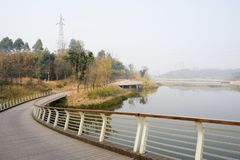 Curving fenced footbridge at riverside in sunny winter. Curving fenced footbridge at the riverside in sunny winter,Chengdu,China royalty free stock image