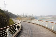 Curving fenced planked footbridge along riverside in sunny winter afternoon. Curving fenced and planked footbridge along the riverside in sunny winter afternoon stock images