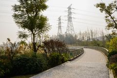 Curving footbridge before pylons on hill in sunny winter afternoon. Curving planked footbridge before electricity pylons on the hill in sunny winter afternoon stock image