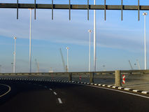 Curving highway. Curving deserted highway with port cranes in background Stock Image