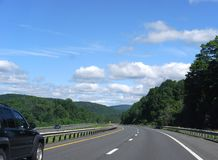 Curving highway. With tree covered hills, freedom of the open road royalty free stock image